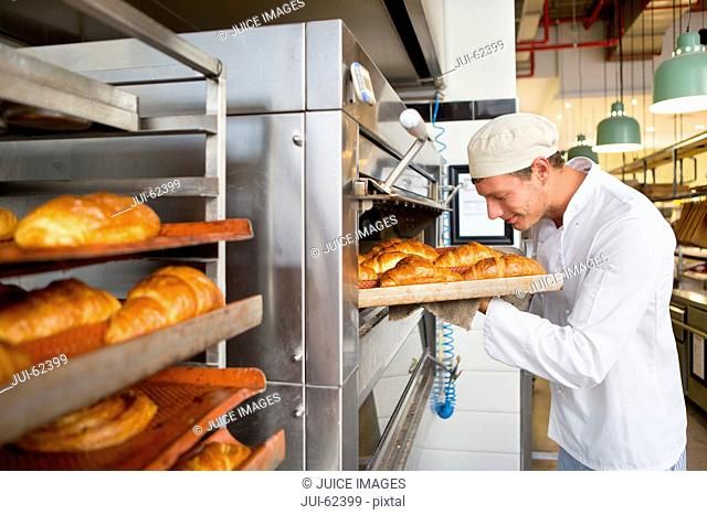 Smiling baker checking tray of bread in bakery kitchen