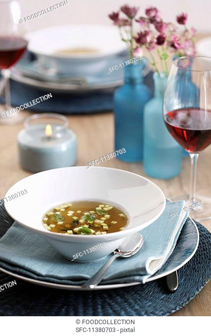 Clear beef broth with garnishes