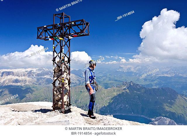 Mountaineer standing next to the summit cross of Marmolada mountain, Dolomites, Passo Fedaia mountain pass, Heiligkreuzkofel group and Sella group at the back