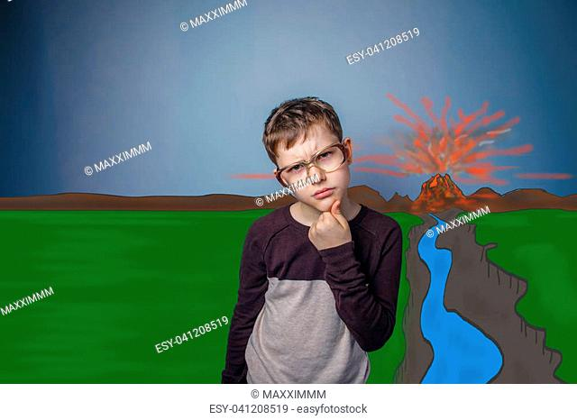 boy in sweater with glasses holds his chin wonders eruption of lava