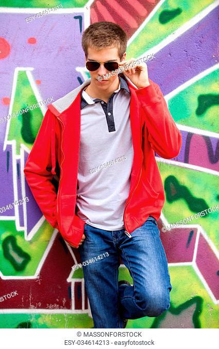 Style teen in glasses standing near graffiti wall