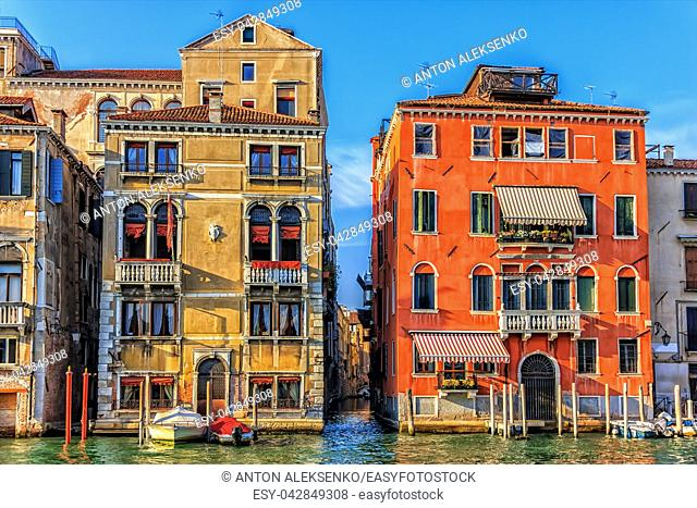 Old venetian palaces and a narrow street channel or rio between them, Venice, Italy