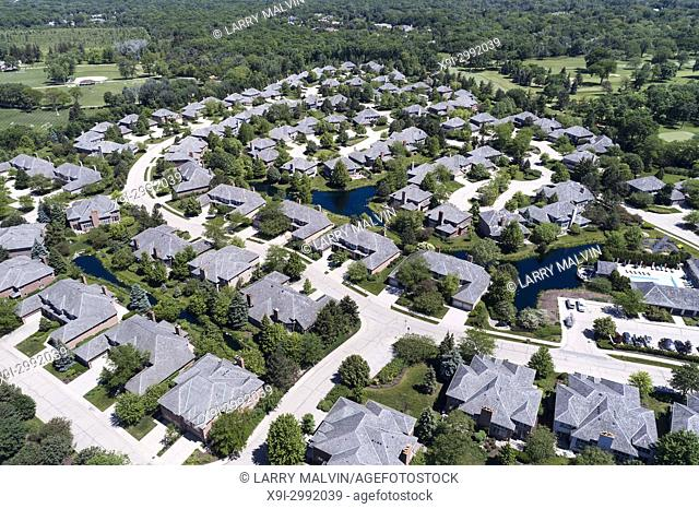 Aerial view of a neighborhood housing complex with ponds in the Chicago suburban city of Northbrook, IL in summer. USA
