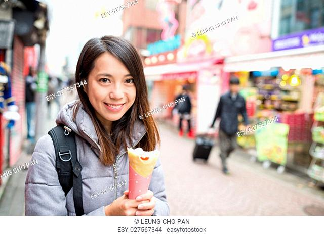 Woman holding a crape cake at street