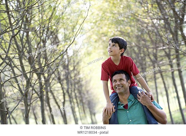 A boy having a piggyback, riding on a man's shoulders