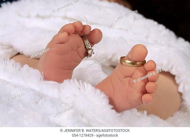 A newborn baby's feet, with the parents' wedding rings on his toes