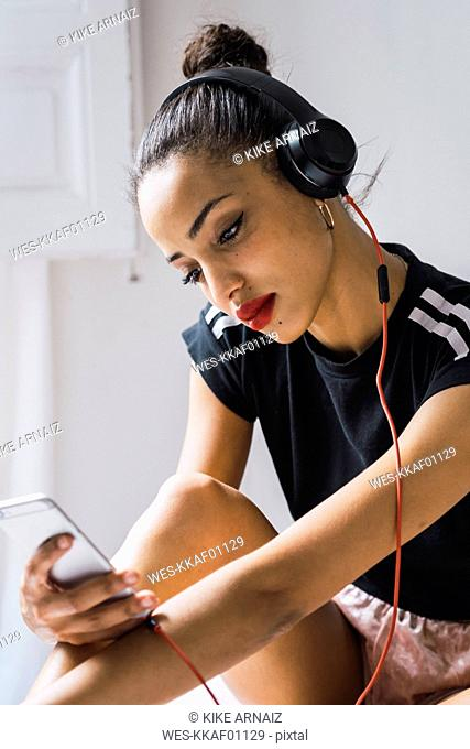 Beautiful young woman sitting down wearing headphones looking at cell phone