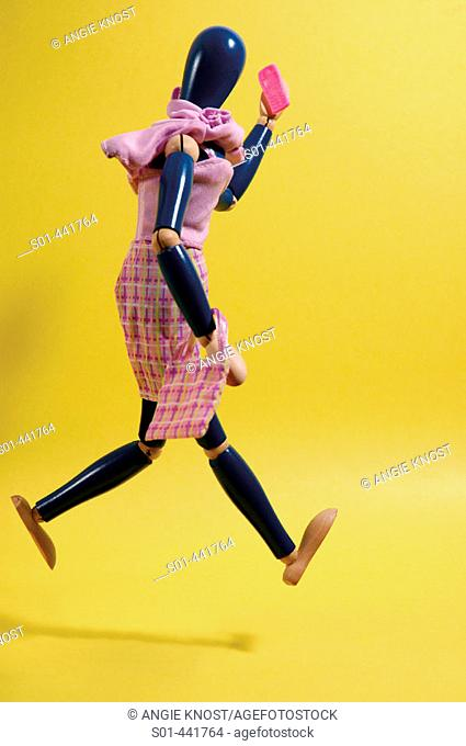 Wooden female figure running, talking on cellular phone and carrying purse