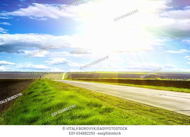 Highway in the hills on a clear sunny day with blue sky and green grass on the roadside