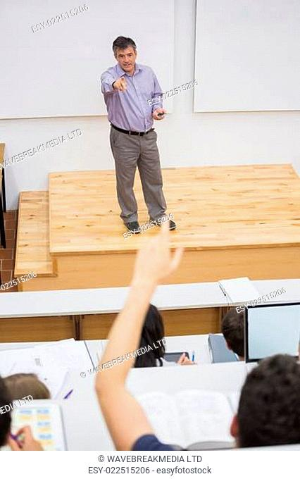 Student in a lecture hall putting hand up