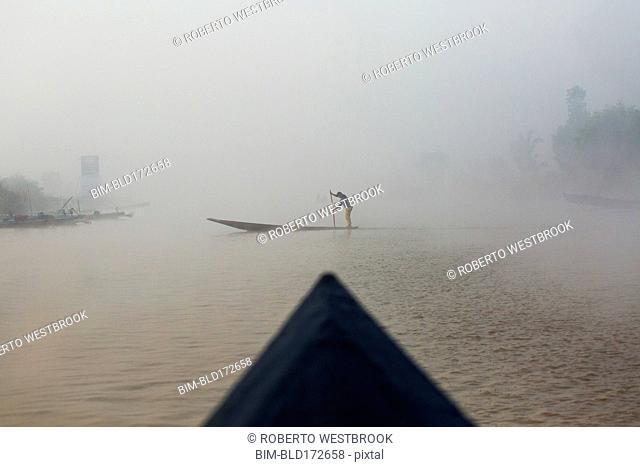 Asian woman rowing canoe on rural lake