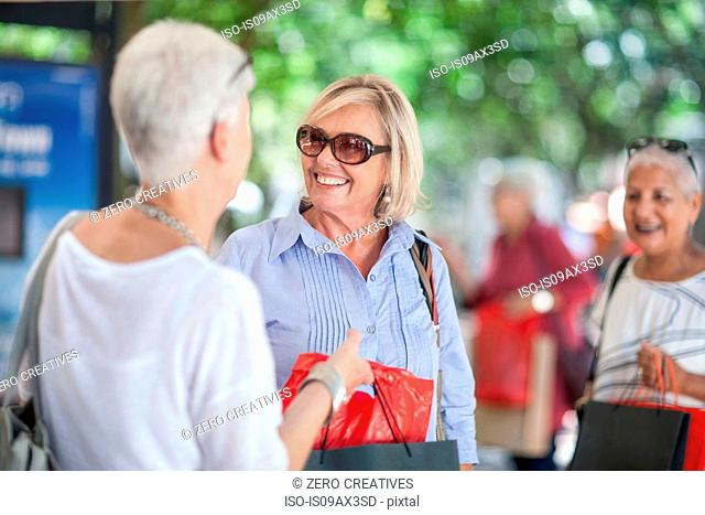 Senior woman and friend shopping and chatting in city