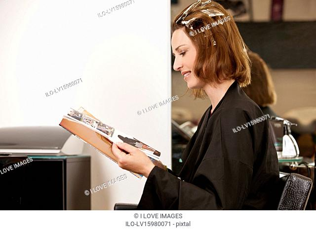 A female client reading a magazine whilst she has her hair coloured in a hairdressing salon, close up