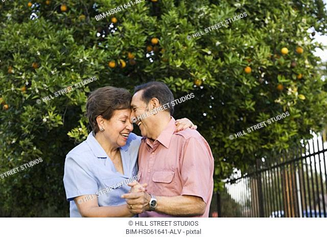 Senior Hispanic couple dancing outdoors