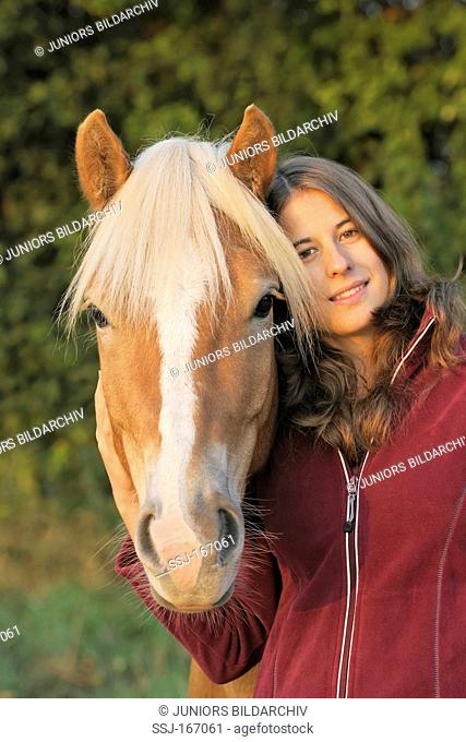 Portrait of young woman and her Haflinger Horse on an early autumn morning. Model release available