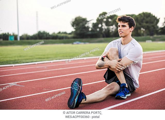 Athlete doing warm-up exercises on a tartan track