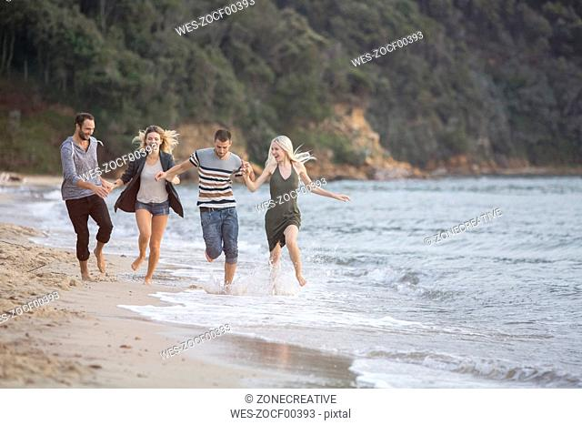 Four happy friends running at the beach