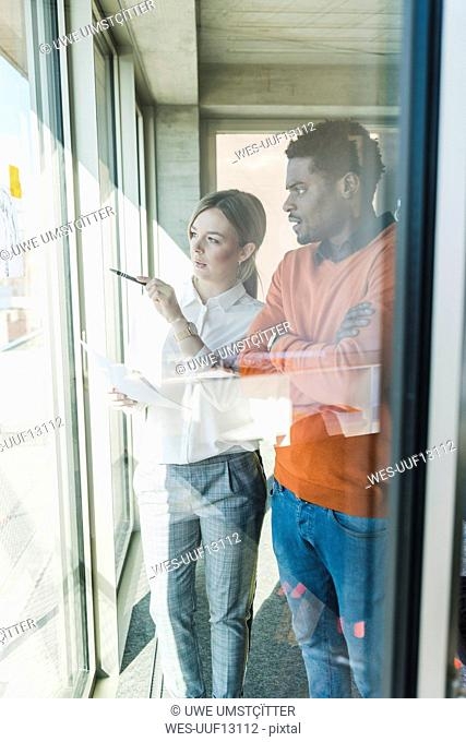 Casual businesswoman and businessman discussing paper at the window