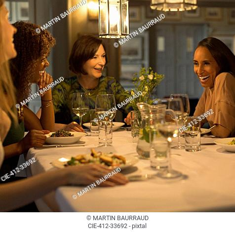Women friends dining and talking at restaurant table
