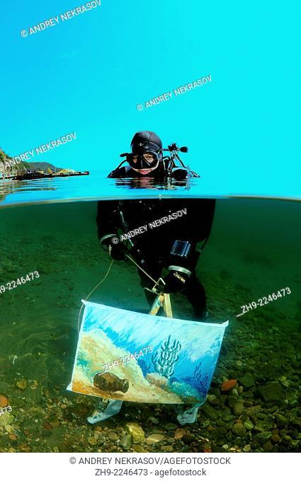 The assistant shows a picture of the artist written by under water artist Yuriy Alexeev (Yuri Alekseev). Lake Baikal, Listvyanka, Irkutsky District