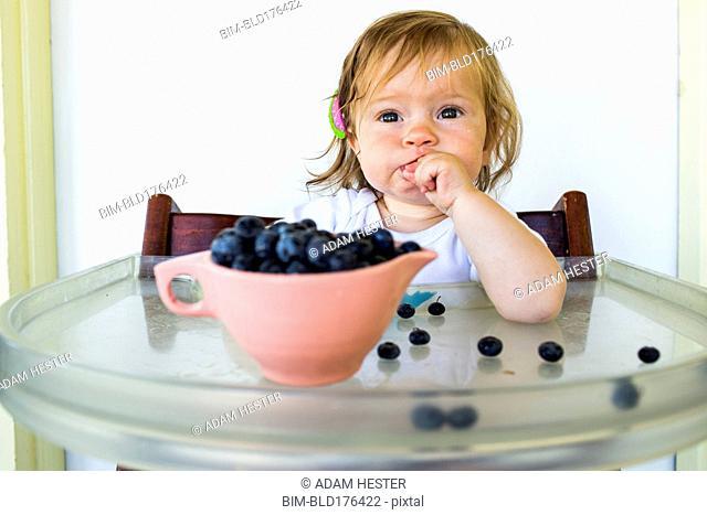 Caucasian baby girl eating blueberries