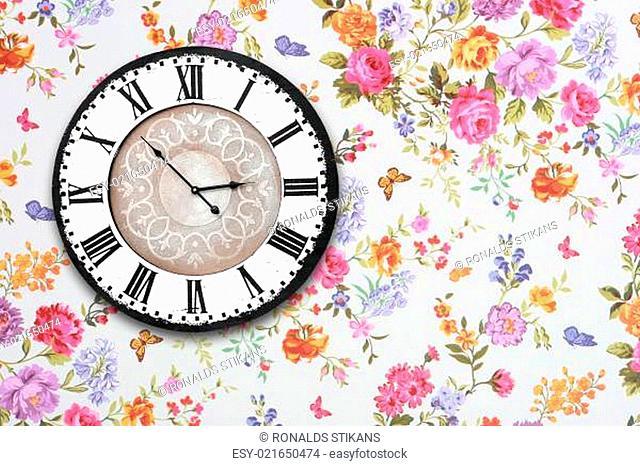 wooden retro clock on floral wallpaper