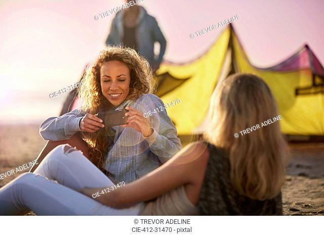 Women using camera phone on beach