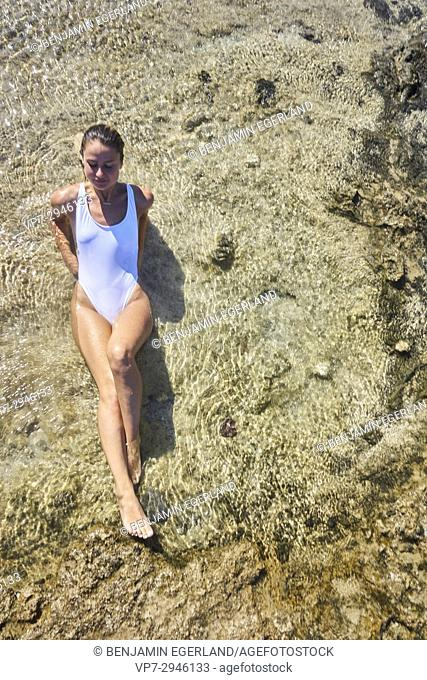 attractive woman relaxing and laying in sea water. Dutch ethnicity. At holiday destination Chrissi Island, Crete, Greece
