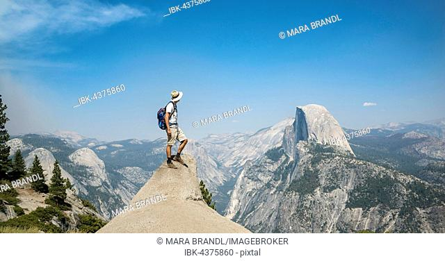 Young man standing on ledge, looking at the Half Dome, view from Glacier Point, Yosemite National Park, California, USA