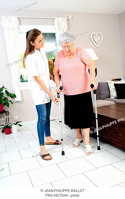 Young physiotherapist nurse helping elderly women physical rehabilitation at home