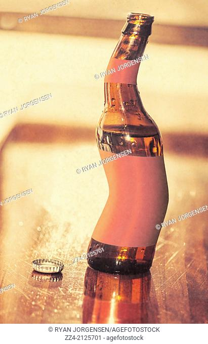 Distorted beer bottle doing a warped dance on wooden bar top. Tipsy