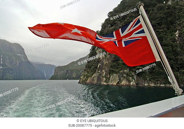 Southland, A New Zealnd Ensign Flag Waves On The Rear Of Real Journeys Cruise Boat The Milford Mariner As It Travels Along Milford Sound In New Zealands...