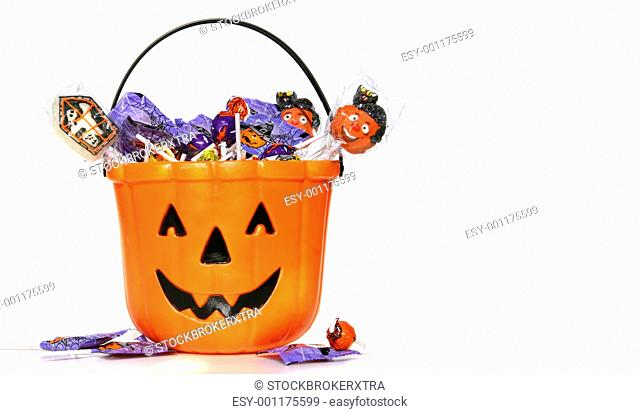 Jack-o-Lantern bucket filled with candies on white background