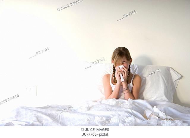 Girl 11-13 sitting upright in bed, blowing nose with handkerchief, front view