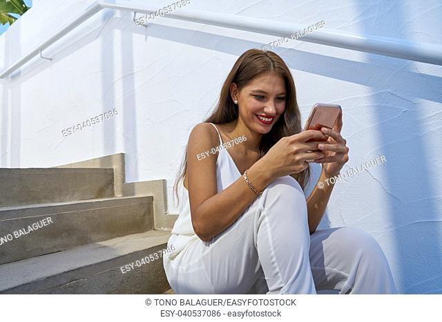 Young latin woman reading smarphone in a white stairway outdoor