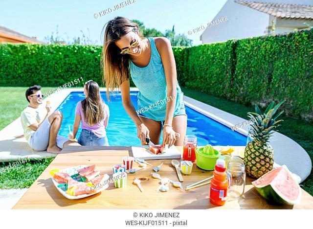 Woman preparing watermelon juice at the poolside with friends in background
