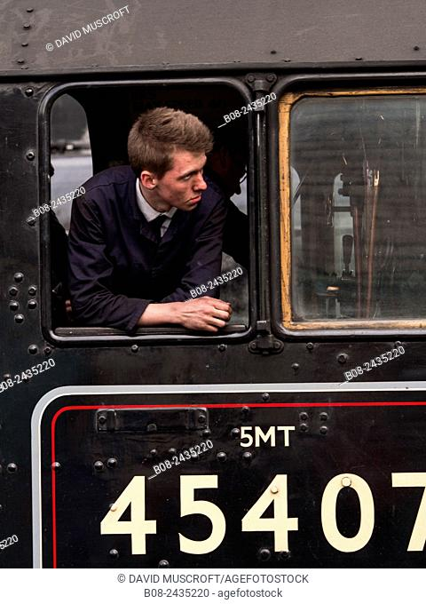 train driver climbs on board steam locomotive at Grosmont station,on The North Yorkshire Moors Railway,Yorkshire,UK