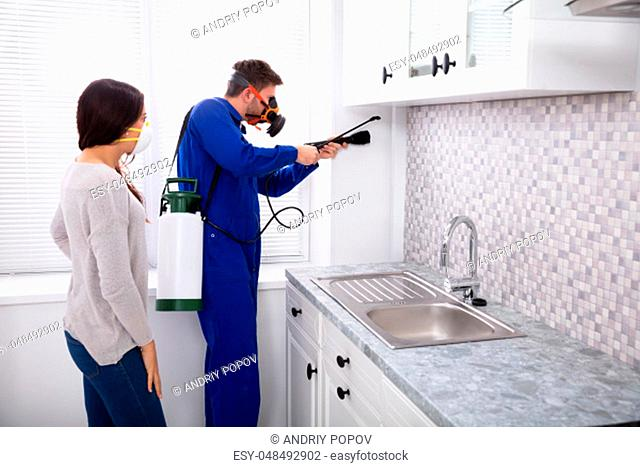 Pest Control Worker And Woman Spraying Pesticide With Torch In Kitchen