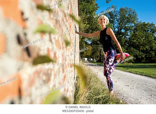 Smiling sportive senior woman stretching at a brick wall