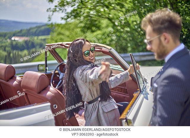 woman waving to man while entering luxury car. Couple enjoying countryside adventure trip in luxury oldtimer. Turkish ethnicity. Blogger Adem Bayalan