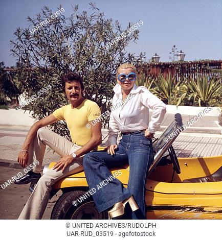 Ein stolzes Paar präsentiert sich und ihren Sportwagen auf Teneriffa, Kanarische Inseln 1975. A proud couple presenting themselves and their sports car on the...
