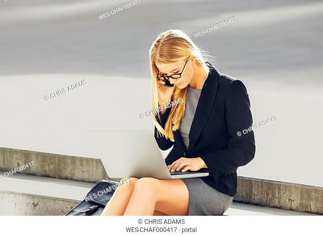Businesswoman sitting on steps using laptop and cell phone