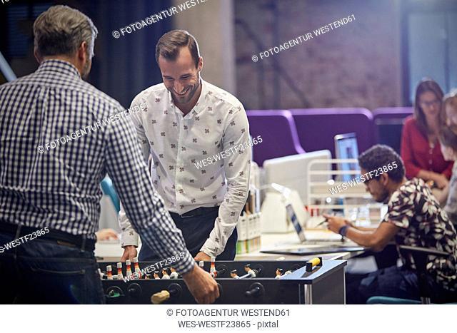 Business people in office taking a break, playing foosball