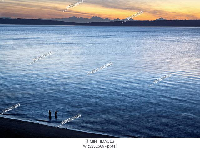 A view from above of a guide and a fly fisherman at the water's edge, fishing for salmon and sea run coastal cutthroat trout at a beach on the north west...