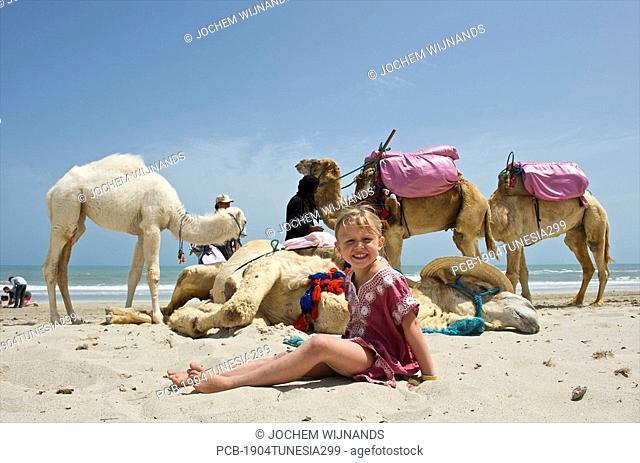 Tunesia, Djerba, Midoun, girl posing for photo together with a camel