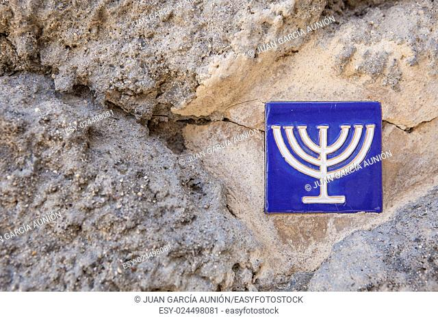 Glazed tile over stone wall with menorah symbol marking the ancient jewish quarter, Toledo, Spain