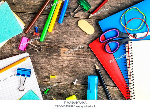 Frame of school supplies on wooden background