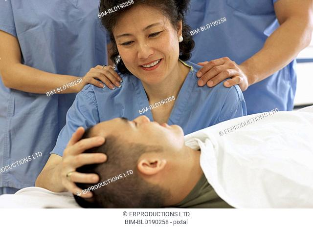 Asian female medical professional smiling at patient