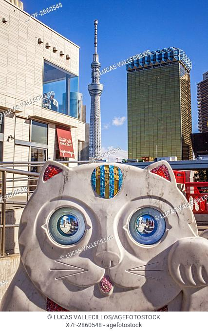 Sculpture of lucky Cat (Maneki Neko), at Azuma bridge, in background Sky Tree Tower, Asakusa District, Tokyo, Japan