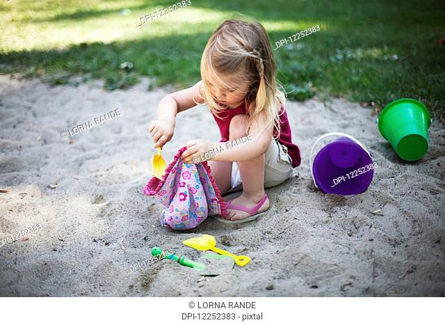 A young girl plays in the sand; Surrey, British Columbia, Canada